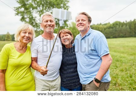 Group of seniors as friends take a selfie with smartphone on selfie stick