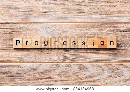 Progression Word Written On Wood Block. Progression Text On Wooden Table For Your Desing, Concept