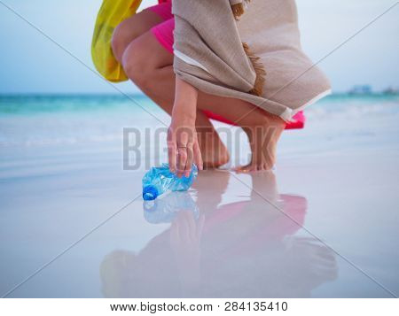 Woman collecting plastic trash on the beach.