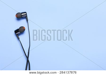 Modern Earphones On Cyan Surface With Copy Space