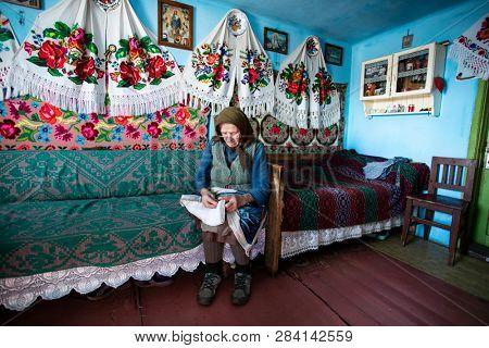 Muntele Bocului, Romania - February 7, 2019: Old rural woman called Lele Maria and her beautiful handworks. Romanian rural environment.