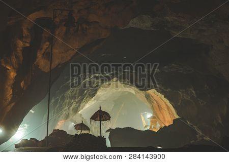 Inside view of the Goa Giri Putri Hindu Temple. Nusa Penida island, Indonesia. The cave interior with the umbrellas, religious attributes. The atmospheric image of the sanctuary.