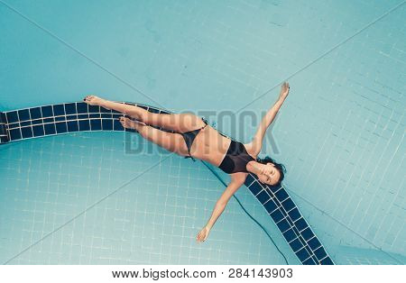 Aerial Top View of Beautiful sexy girl in a black bikini lying on the edge of the swimming pool with transparent turquoise water. Relax, sunbathing, fun, holidays, resort on tropical island