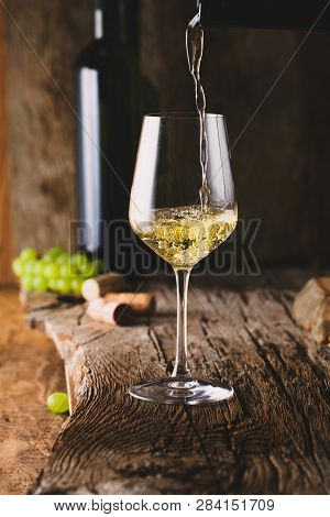 Wine. Glass Of White Wine In Wine Cellar. Old White Wine On Wood. Wine Pouring Froma Bottle