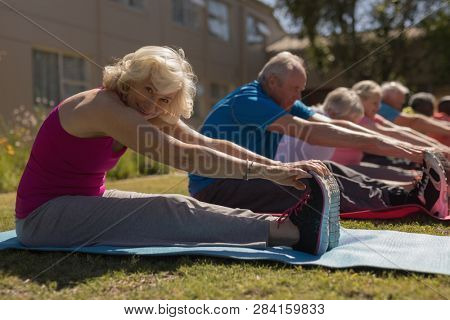 Side view of group of active senior people exercising in the park with senior woman looking at the camera