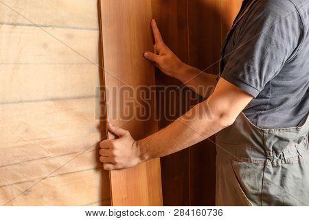 Man In Construction Clothing Sets Medium Density Fiberboard Panels On The Wall