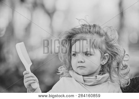 Kid With Long Blond Hair Hold Comb On Natural Background. Girl Beauty, Look, Hairstyle, Care, Health