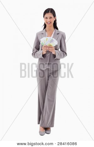 Smiling businesswoman holding money against a white background