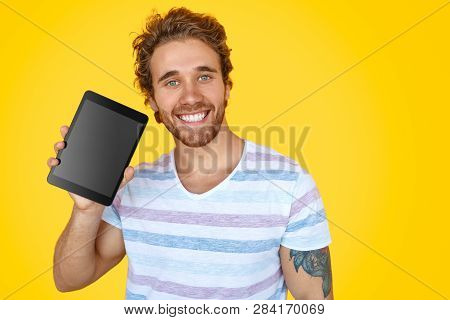 Happy Tattooed Hipster In Casual T-shirt Demonstrating New Touchpad At Camera On Yellow Background