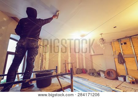 Worker Is Working With Palette-knife For Flattening  The Ceiling From Wooden Platform In Room Of  Ap