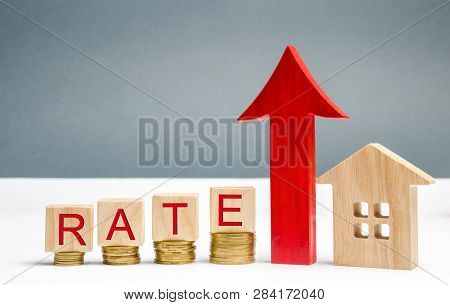 Wooden Blocks With The Word Rate, Up Arrow And Wooden House. The Concept Of Raising Interest Rates O