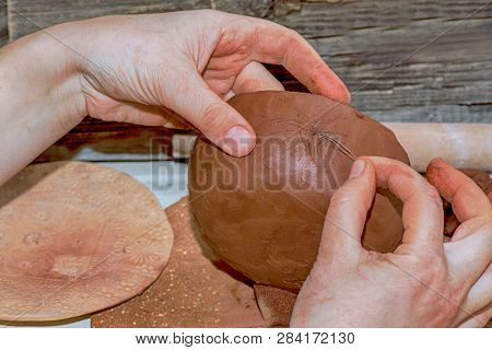 Hands Of The Ceramist Make A Product From Brown Clay And Print On It A Print From A Dry Grass.