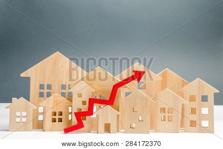 Wooden Houses And Up Arrow. The Concept Of Real Estate Market Growth. The Increased In Housing Price