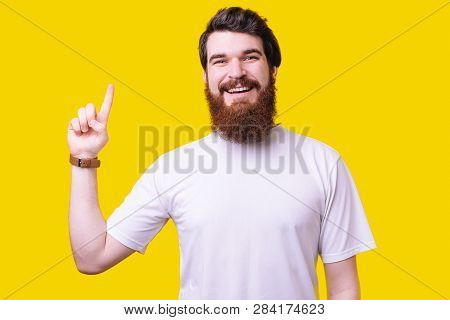 Portrait Of An Cheerful Bearded Man Pointing Finger Up At Copyspace Isolated Over Yellow Background