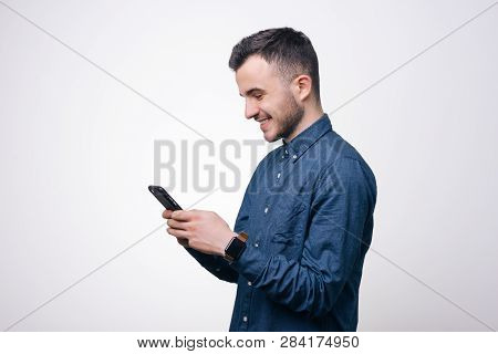 Smart Casual Ypung Man In Blue Shirt Using Smartphone In Studio Over White Background