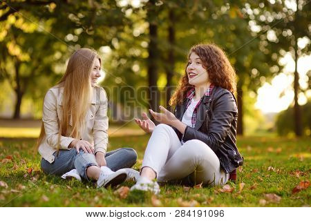 Two Beautiful Young Women Talking While Sitting On The Ground At Sunny Park. Girlfriends. Communicat