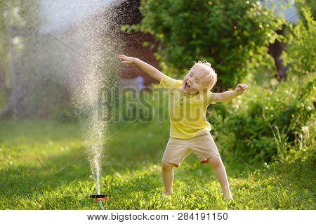 Funny Little Boy Playing With Garden Sprinkler In Sunny Backyard. Preschooler Child Having Fun With