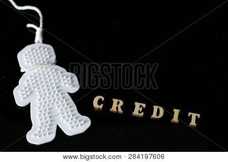 A Credit Word Is Laid Out Wooden Letters. A Plastic Man Hung Himself On A Rope. Credit History And S
