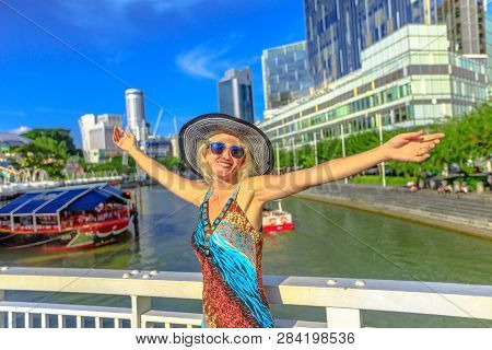 Happy tourist woman with wide hat enjoying at Clarke Quay and Riverside area in Singapore, Southeast Asia. Cruise on Singapore River in sunny day with skyscrapers downtown on background. poster