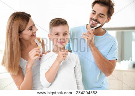 Happy Family With Toothbrushes In Bathroom. Personal Hygiene