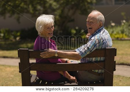 Rear view of active senior couple sitting together on the bench and smilling at the camera in the park
