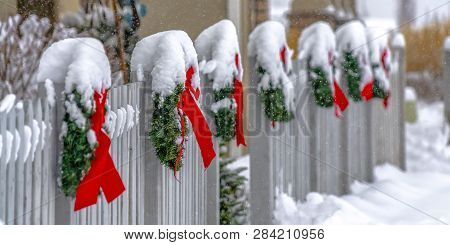 White Fence Lined With Christmas Wreaths In Utah