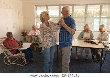 Side view of active senior couple dancing with senior people reading at nursing home