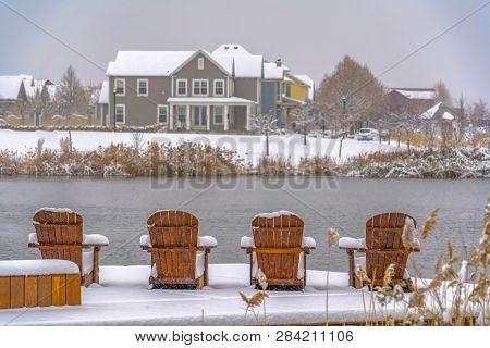 Wooden Chairs On Snowy Lake Deck In Daybreak Utah