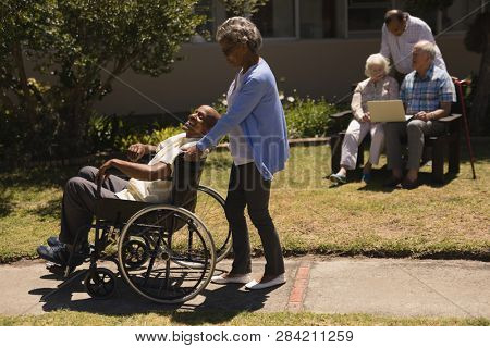 Front view of senior woman pushing happy senior man in a wheelchair on sunny day  in garden