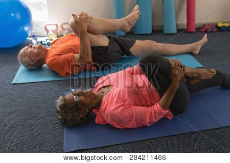 High angle view of determined senior couple exercising gym excercie in fitness studio