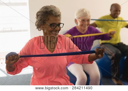 Happy senior woman exercising with resistance band in fitness studio