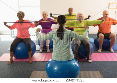 Front view of young female trainer and senior people exercising with resistance band in fitness studio