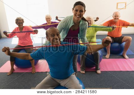 Front view of happy young female trainer assisting senior man in fitness studio
