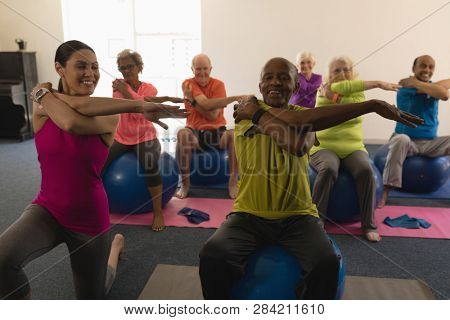 Front view of senior people exercising with female trainer in fitness studio