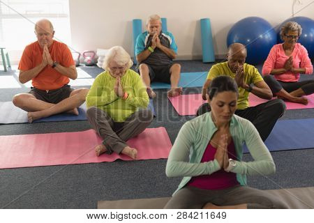 Front view of concentrated senior people doing yoga with female trainer in fitness studio
