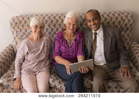 Front view of happy senior friends with digital tablet sitting on sofa and looking at camera in home