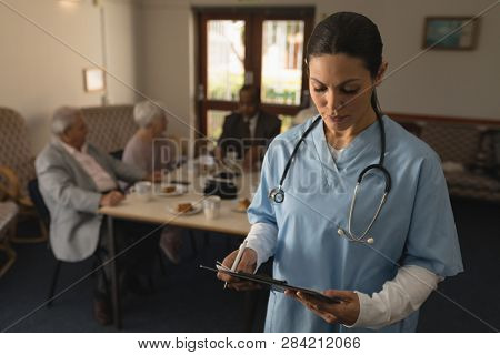 Front view of young female doctor looking at clipboard with her patient behind her at nursing home