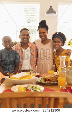 Portrait of happy African American family looking at camera at dining table in their comfortable home