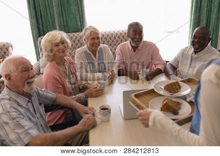 Front view of group of happy senior people having black coffee with cake in living room at home