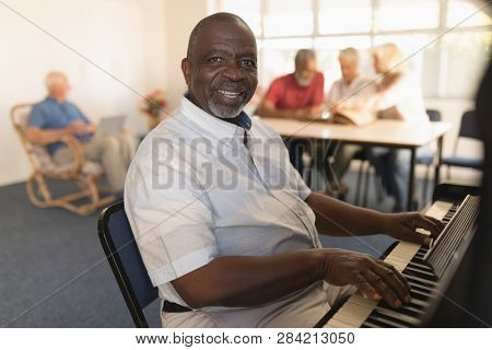 Side view of happy active senior man playing piano with senior people behind at nursing home