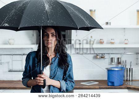 Amazed Woman Standing Under Umbrella During Leak In Kitchen