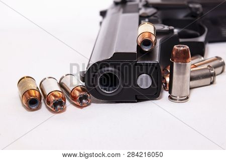 A Black 40 Caliber Pistol With Eight 40 Caliber Hollow Point Bullets On A White Background