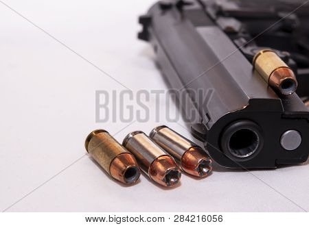 A Black 40 Caliber Pistol With Four 40 Caliber Hollow Point Bullets On A White Background