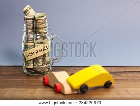 Money for car insurance in jar with two wooden car in accident