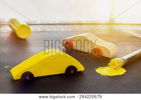 Toy cars with yellow paint brush and sunbeamfrom window