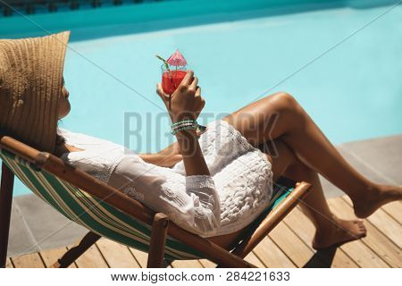 Side view of young African American woman with cocktail glass relaxing on sun lounger in backyard on a sunny day. She seems to be on vacation.
