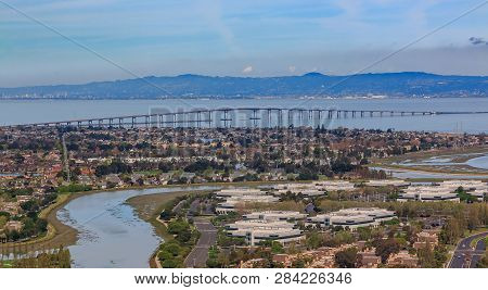 Aerial View From An Airplane Of San Mateo Hayward Bridge Across The San Francisco Bay And Foster Cit