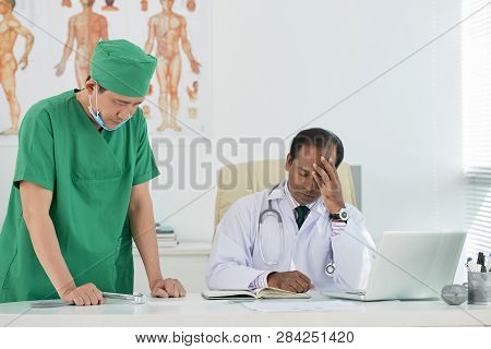 Surgeon Informing Chief Physician About Lethal Surgical Outcome