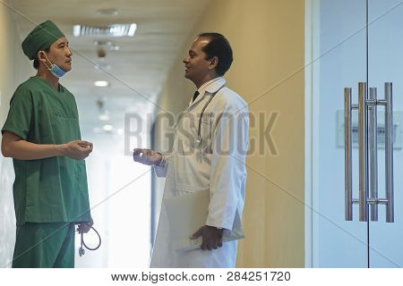 Physician And Surgeon Standing In Hospital Corridor And Discussing Difficult Case