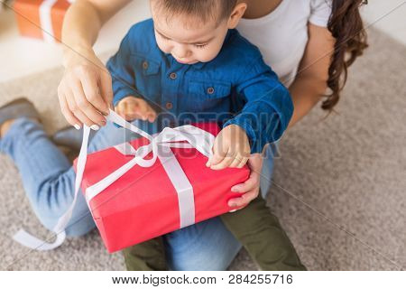 Present, Children, Birthday And Holiday Concept - Little Child Boy Unpacking Gift Box With Mom